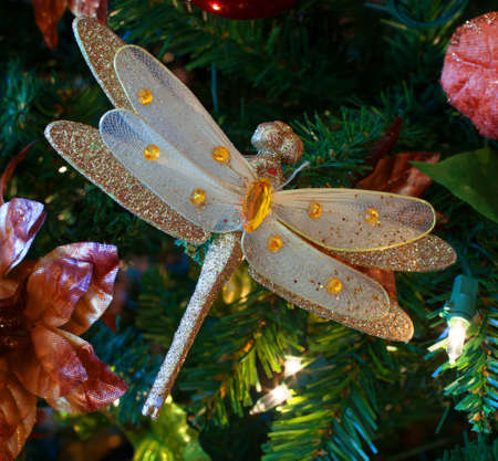 fake christmas tree: Large dragonfly ornament in an artificial Christmas tree