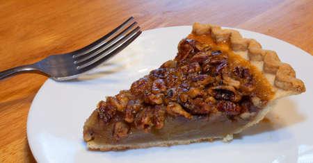 pecan pie: Gran rebanada de pastel de nuez y un tenedor en un plato