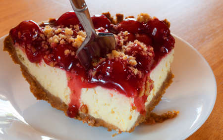 graham: Fork going for the first bite in a cherry covered cheesecake with graham cracker crust