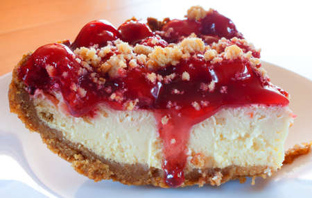 graham: Large slice of cheesecake with graham cracker crust and cherry topping