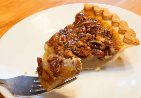 pecan pie: Pastel de nuez en un plato con una buena raci�n de un tenedor