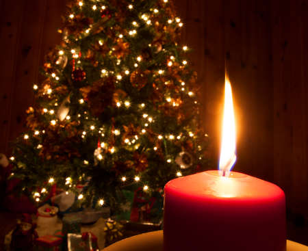 Bright candle burning in front of a Christmas tree photo
