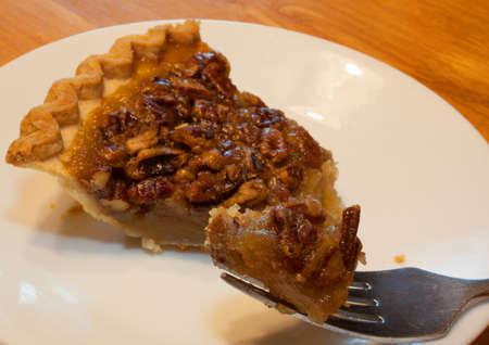 pecan pie: Gran pedazo de pastel en un tenedor con pastel de nuez detr�s Foto de archivo
