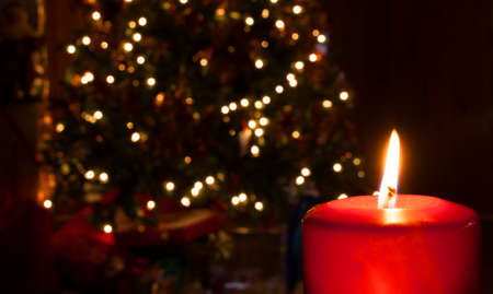 Red candle burning brightly in front of a lit Christmas tree photo
