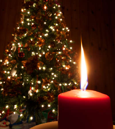 Flame coming from a red candle in front of a Christmas tree photo