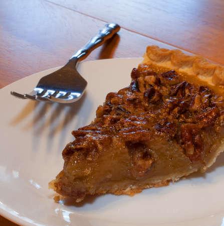 pecan pie: Rebanada de pastel de nuez y un tenedor sobre un plato blanco