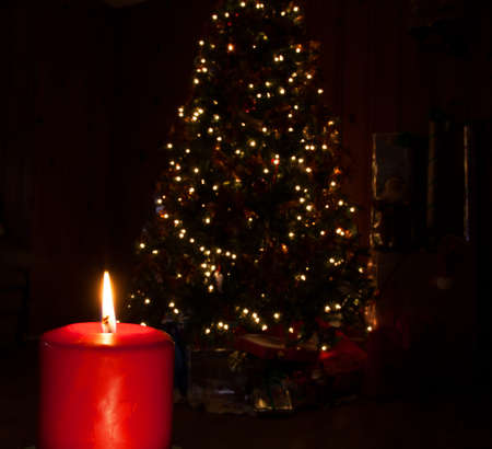 Candle burning brightly in front of a Christmas tree with presents photo