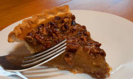 pecan pie: Tenedor sobre un plato blanco listo para sumergirse en pastel de nuez