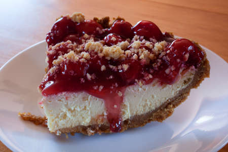 graham: Cheesecake with cherry topping and graham cracker crust on a plate