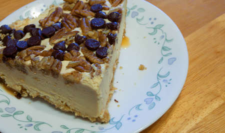 Cheesecake topped with nuts and chocolate chips on a white plate Imagens