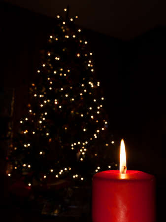 Bright red candle in front of a decorated Christmas tree photo