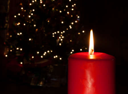 Flame coming from a red candle brighter than the Christmas tree behind photo