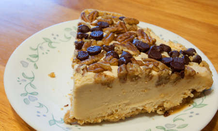 chocolate chips: Slice of cheesecake with nuts and chocolate chips on top