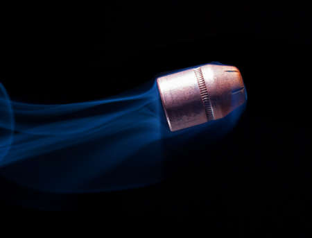 projectile: Flat nosed handgun bullet heading up with smoke behind