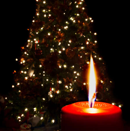 Single Red Candle Burning In Front Of A Lighted Christmas Tree Stock ...