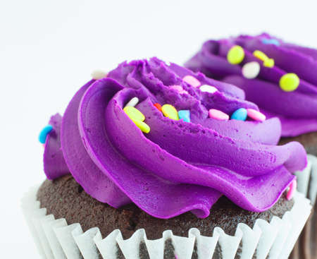 Thick and sweet purple frosting on cupcakes photo