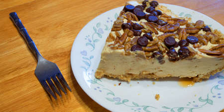 chocolate chips: Slice of cheesecake with walnuts and chocolate chips on top