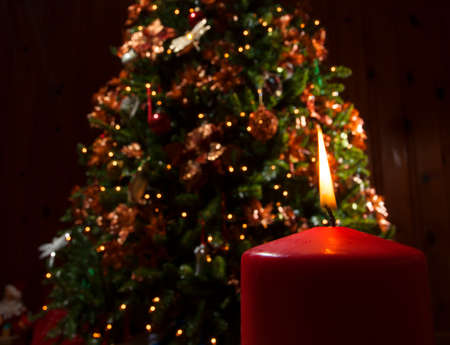 Red candle and flame in front of a decorated Christmas tree photo