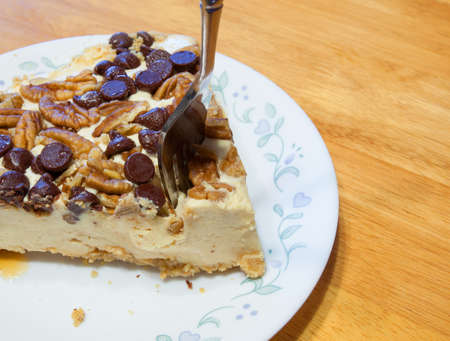 chocolate chips: Cheesecake with nuts and chocolate chips with a fork going in
