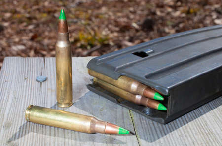 tipped: Magazine on wood planks with green tipped metal ammo