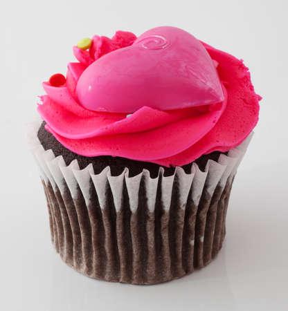 plastic heart: Cupcake al cioccolato che ha glassa rosa e un cuore di plastica