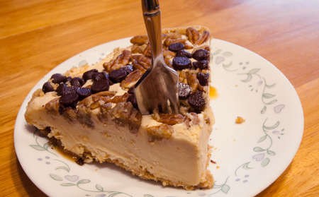 chocolate chips: Fork inside cheesecake covered with chocolate chips and nuts