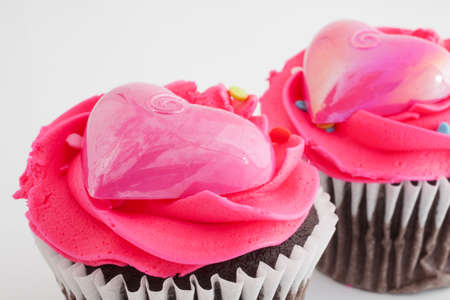 frosting': Two chocolate cupcakes with pink frosting and plastic hearts