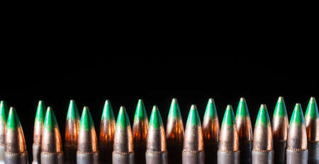 tipped: Line of cartridges that have green tipped bullets on top Stock Photo