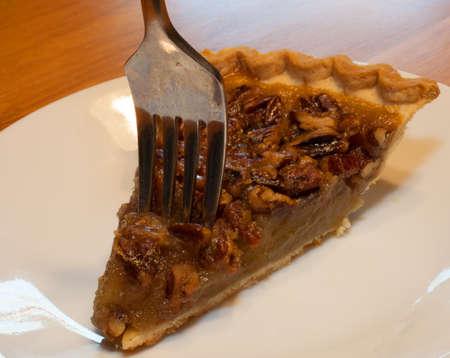 pecan pie: Tenedor de sumergirse en un pedazo de pastel de nuez en un plato blanco Foto de archivo