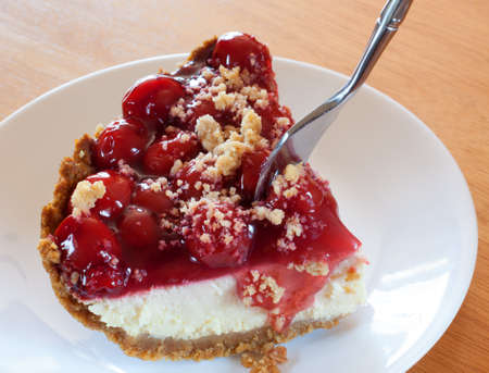 Fork diving into a cheesecake with graham cracker crust and cherries