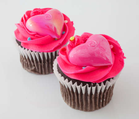 frosting': Two chocolate cupcakes on white with pink frosting