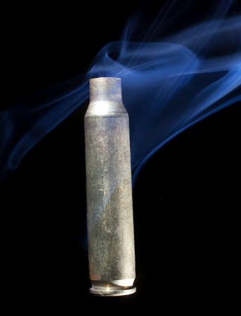 the casing: Brass casing from ammunition that has been fired and is smoking