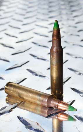 tipped: Cartridges with green tipped bullets on chrome armor plate aluminum