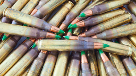 tipped: Cartridges in a heep that has green tipped bullets Stock Photo