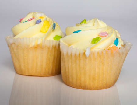 Two yellow frosted cupcakes that are on a white background photo