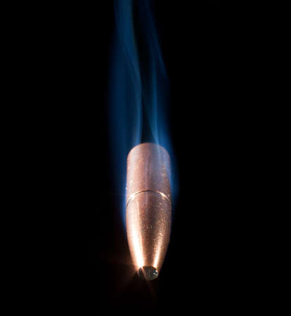 projectile: Copper plated bullet with trailing smoke that looks like it is coming at the viewer Stock Photo