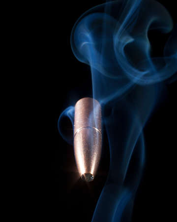 Thirty caliber bullet with smoke behind with a black background