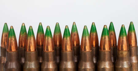 tipped: Two rows of rifle cartridges that have green tipped bullets on a white background Stock Photo