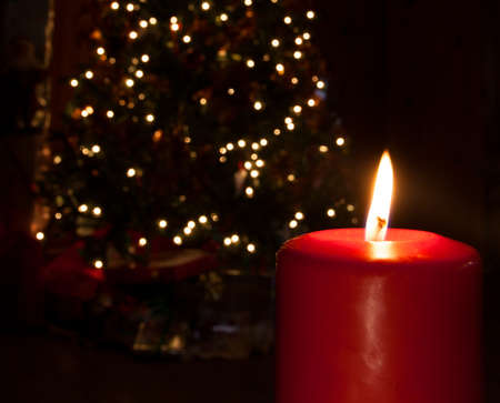 Candle in front of a Christmas tree that is lit photo