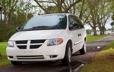 Mini van that is at the end of a gravel driveway with water photo