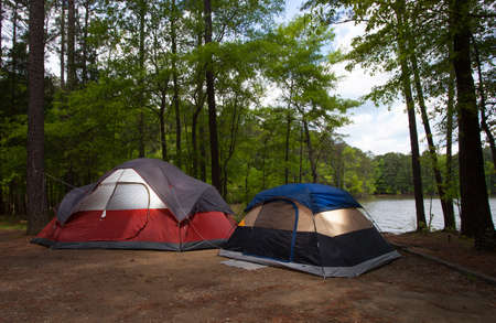 pitched: Two colorful tents pitched next to a lake just before sunset