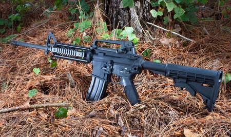 semi automatic: Black semi automatic rifle on a forest floor Stock Photo