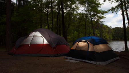 pitched: Two nylon tents pitched in a campsite at dusk with a lake nearby Foto de archivo