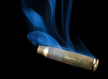 the casing: Casing from a rifle cartridge that has been shot and has smoke Stock Photo