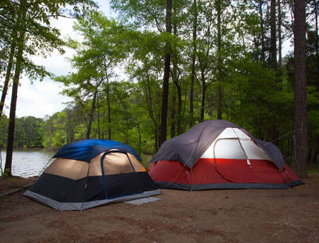 pitched: Two tents pitched by a lake with nightfall soon to arrive