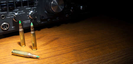 tipped: Two way radio with three green tipped rifle cartridges Stock Photo