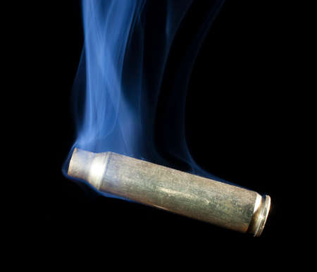 the casing: Casing from a rifle cartridge that has been shot and is smoking