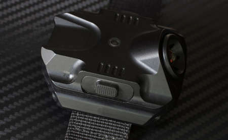 Side view of a tactical flashlight and activation button that is worn on the arm