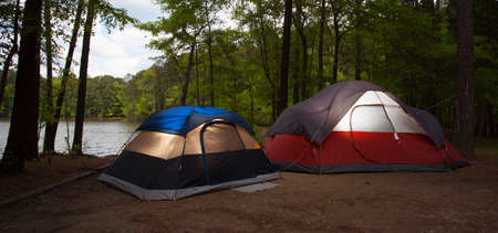 pitched: Tents that are pitched in a campsite next to a lake before sunset