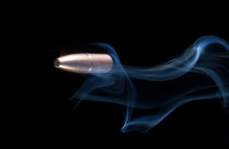 projectile: Copper plated bullet on a black background with smoke Stock Photo